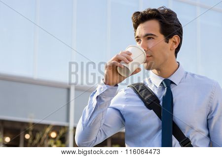 Successful young businessman outside office. Businessman drinking coffee and thinking about his future. Happy ambitious man drinking an hot coffee with a paper cup in front of the modern building.