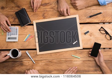 Close up of empty blackboard placed on wooden table with colored chalks. High angle view of blank blackboard on business desk. Businesspeople using blackboard during a meeting.