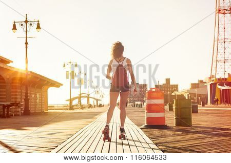Young stylish woman skating on footpath during sunset. Young sporty girl rollerblading on skates. Young woman in casual skating on the footpath during summer sunset in a urban landscape.