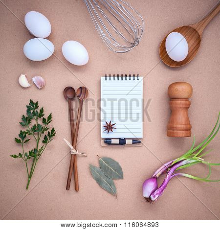 Four White Eggs With Note Book ,pepper Bottle ,wooden Spoons ,bay Leaf Parsley And Wire Whisk Set Up