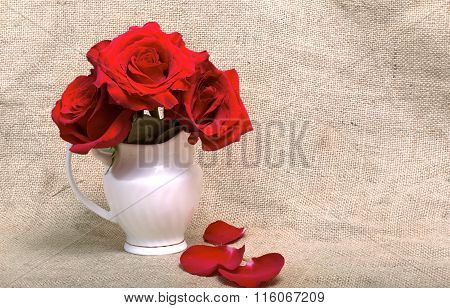Red Roses In A White Jug Against A Sacking