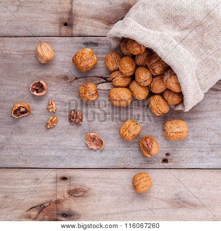 Walnuts Kernels In Hemp Sack And Whole Walnuts On Rustic Old Wooden Background.