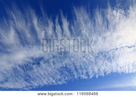 Background photo of natural Cirrus Clouds formation on a blue sky during winter in Europe