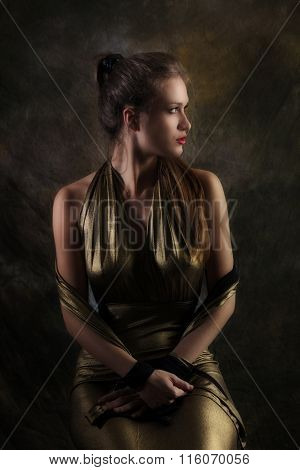 young woman in golden dress studio shot, profile