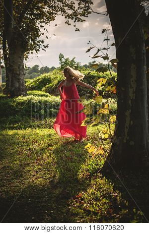 young woman in long red dress run  through the woods, summer day, natural light, full body shot