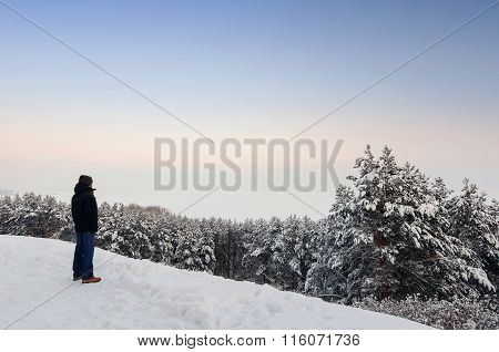 Tourist in blue jeanes and dark jacket standing on hill