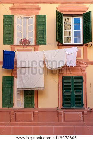 Shutters, Fake Windows And Clothes Hanging On A Mediterranean Facade