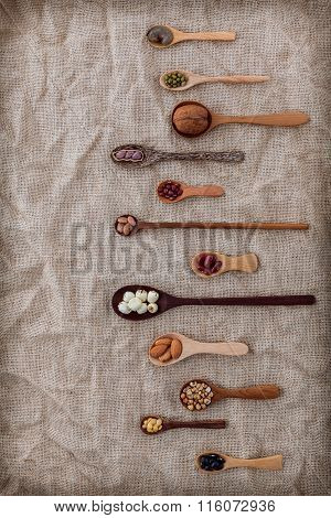 Various Beans And Nuts In The Wooden Spoon On Brown Cloth Sack Background. Mung Bean, Groundnut, Soy