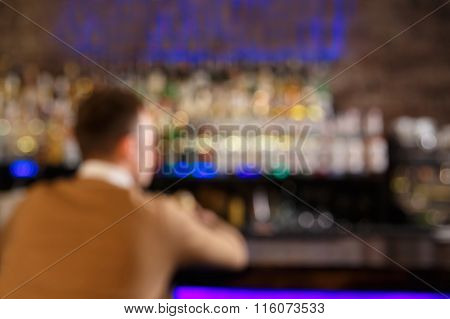 Blured Picture With Man Sitting At The Bar