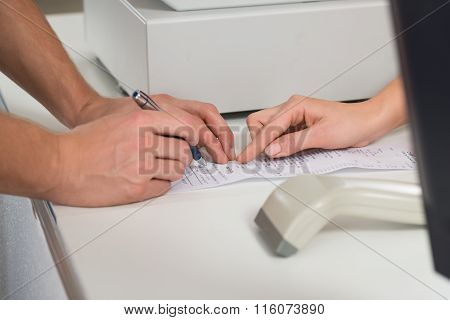 Customer's Hands Signing On Receipt At Counter In Store