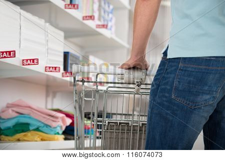 Man Standing With Shopping Cart In Supermarket