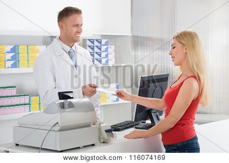 Woman Giving Prescription To Pharmacist