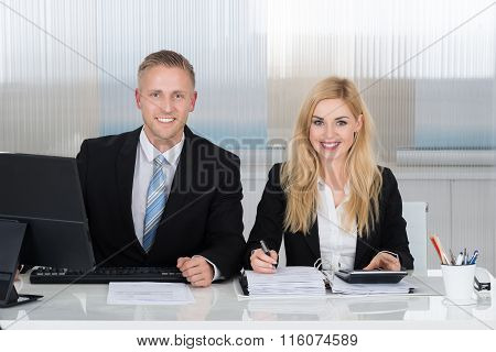 Smiling Accountants Calculating Finance At Desk In Office