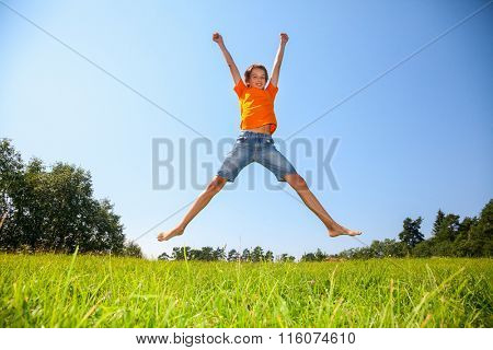 Kid jumping on the sunny meadow in a summer forest