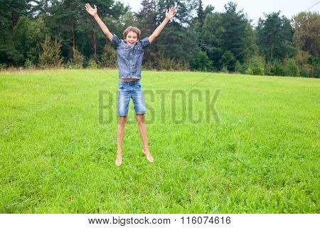 Kid jumping on the meadow in a summer forest