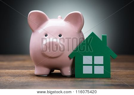 Green Paper House And Piggybank On Table