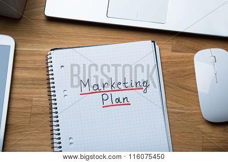 Marketing Plan Written On Notepad At Office Desk