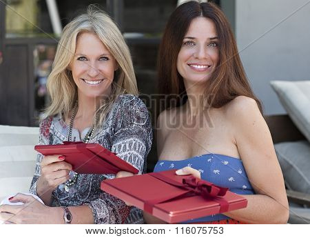 Beautiful middle age women with gifts sitting outdoors