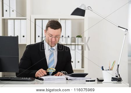 Accountant Analyzing Invoice With Magnifying Glass