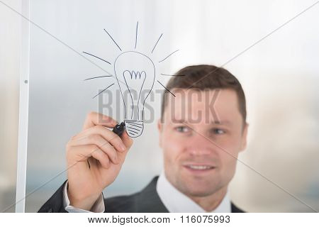 Businessman Drawing Lightbulb On Glass Wall In Office