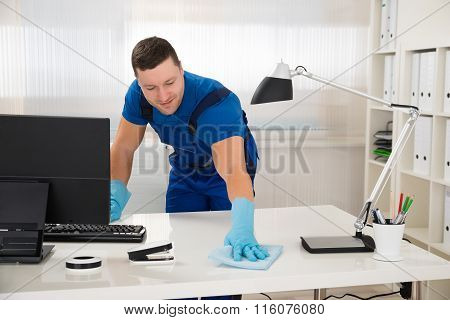 Worker Cleaning Desk With Sponge