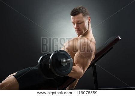 Determined Man Exercising With Dumbbells On Chair