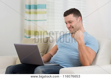 Man Clenching Fist While Using Laptop On Sofa