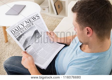 Man Reading Weather News On Newspaper At Home