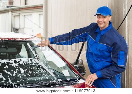 Worker Washing Windshield Of Car At Service Station