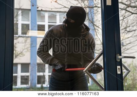 Hooded Man Using Crowbar To Open Glass Door