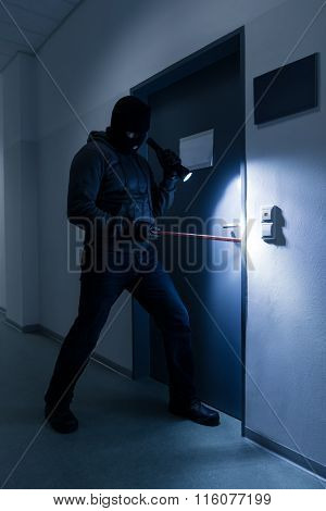 Thief With Flashlight Trying To Break Office Door