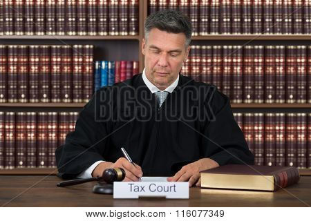 Tax Court Nameplate On Table With Judge Writing In Courtroom
