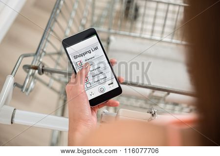 Woman Checking Shopping List On Smartphone In Supermarket