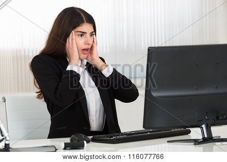 Shocked Businesswoman Looking At Computer Monitor At Desk