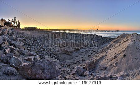 Pier between the sand and rock dunes.