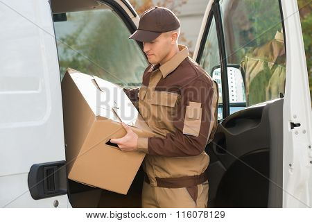 Delivery Man Removing Cardboard Box From Truck