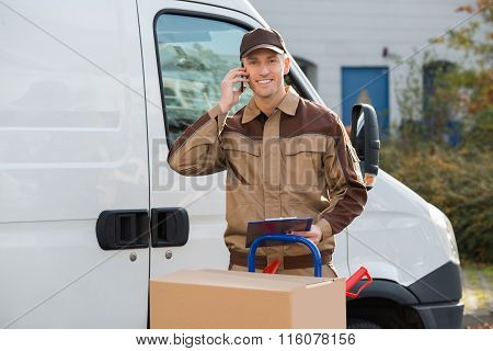 Delivery Man Using Mobile Phone Against Truck