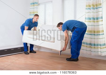 Movers Placing Sofa On Floor At Home