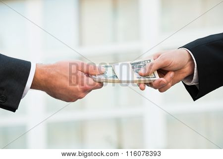 Businessman Giving Bribe To Partner