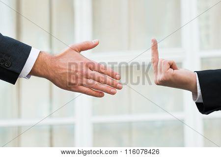 Businessman Showing Middle Finger To Partner Offering Handshake