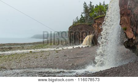 Springtime Nova Scotia coastline in June.   Waterfalls from cliff onto rocky pebble beach.