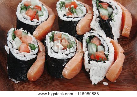 fresh sushi sashimi nigiri with raw salmon slice red ginger and japanese vinegar on wooden plate over white table