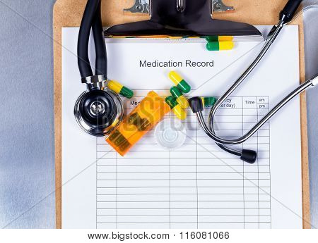 Clipboard With Patient Medication Record Plus Pills And Equipment On Counter
