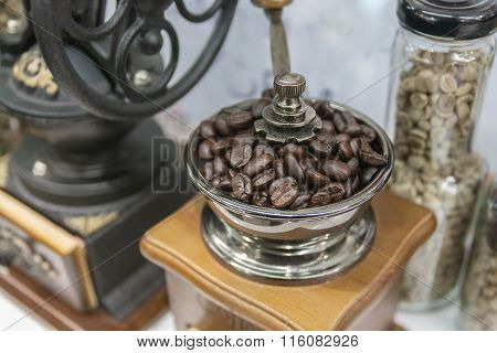 Closeup Coffee Grinder And Coffee Beans On Blurred Background