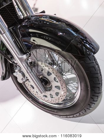 The front tire of a parked custom motorcycle