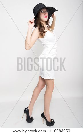 Beautiful sexy slim woman in a little white dress and broad black hat