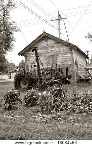 old tractor parked behind a small town garage(black and white)