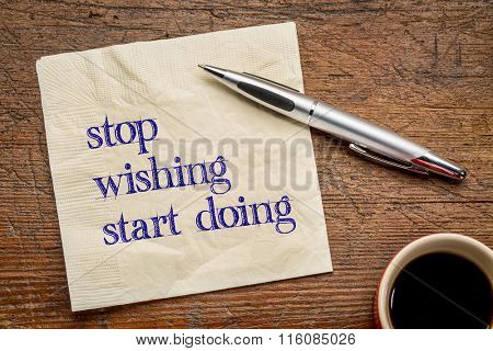 stop wishing, start doing - motivational text on a napkin against grunge wood  grunge wood table, top view with coffee