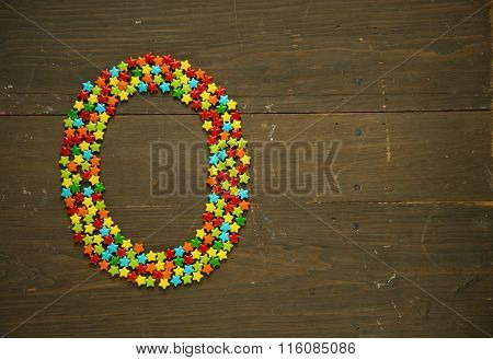 Letter O from alphabet made with star shape candy on a wooden background
