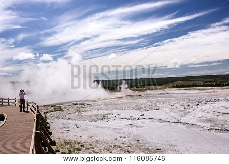 Visitors stroll along boardwalks through Midway Geyser Basin in Yellowstone on a summer morning.